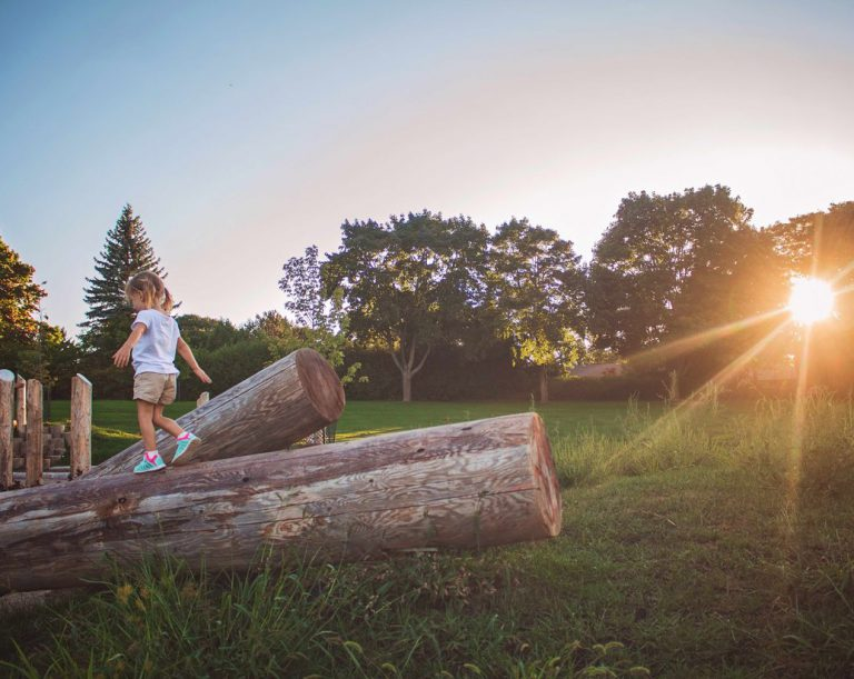 Child playing on Earthscape playground at sunset