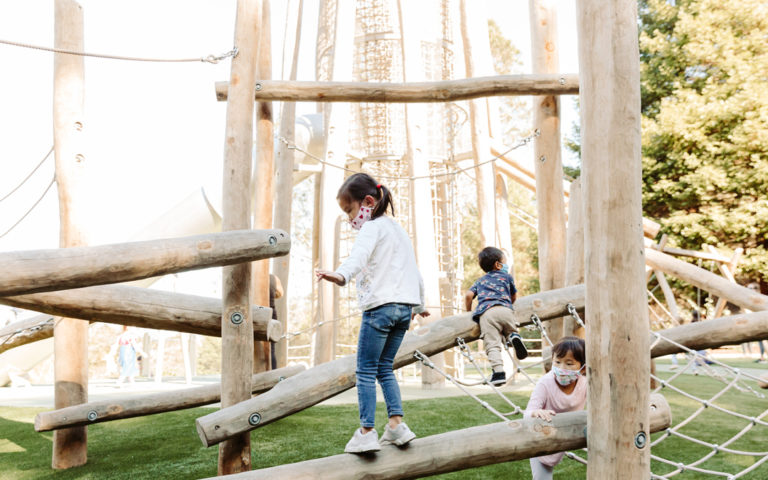 natural wood playground with spiral log jam climber net climber balance