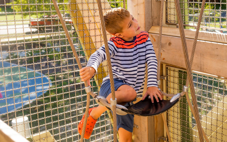Child sits in sling seat inside John Ball Zoo playground tower