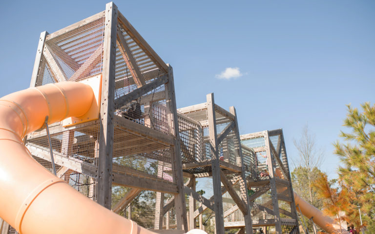 Pine Cove Park natural wood playground timber towers tube slides net rope climbers