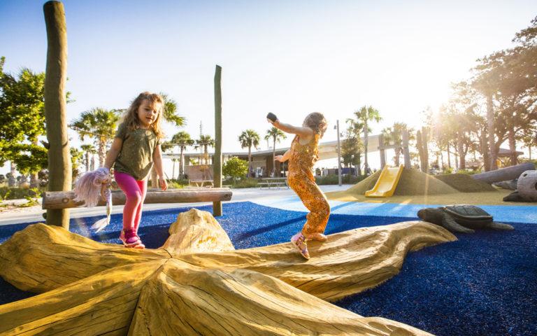 girls running on starfish sculpture St. Pete playground